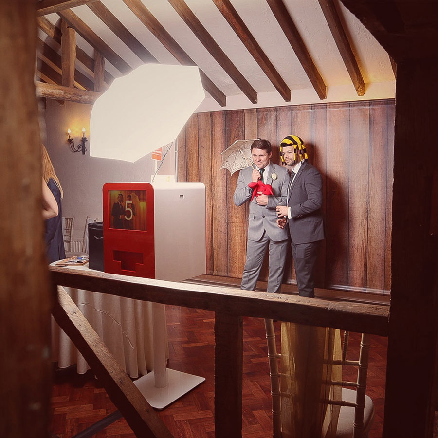 Photo booth at wedding with wooden backdrop